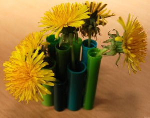 green vase with dandelions
